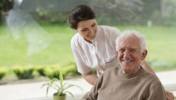 Elderly male with female carer by window