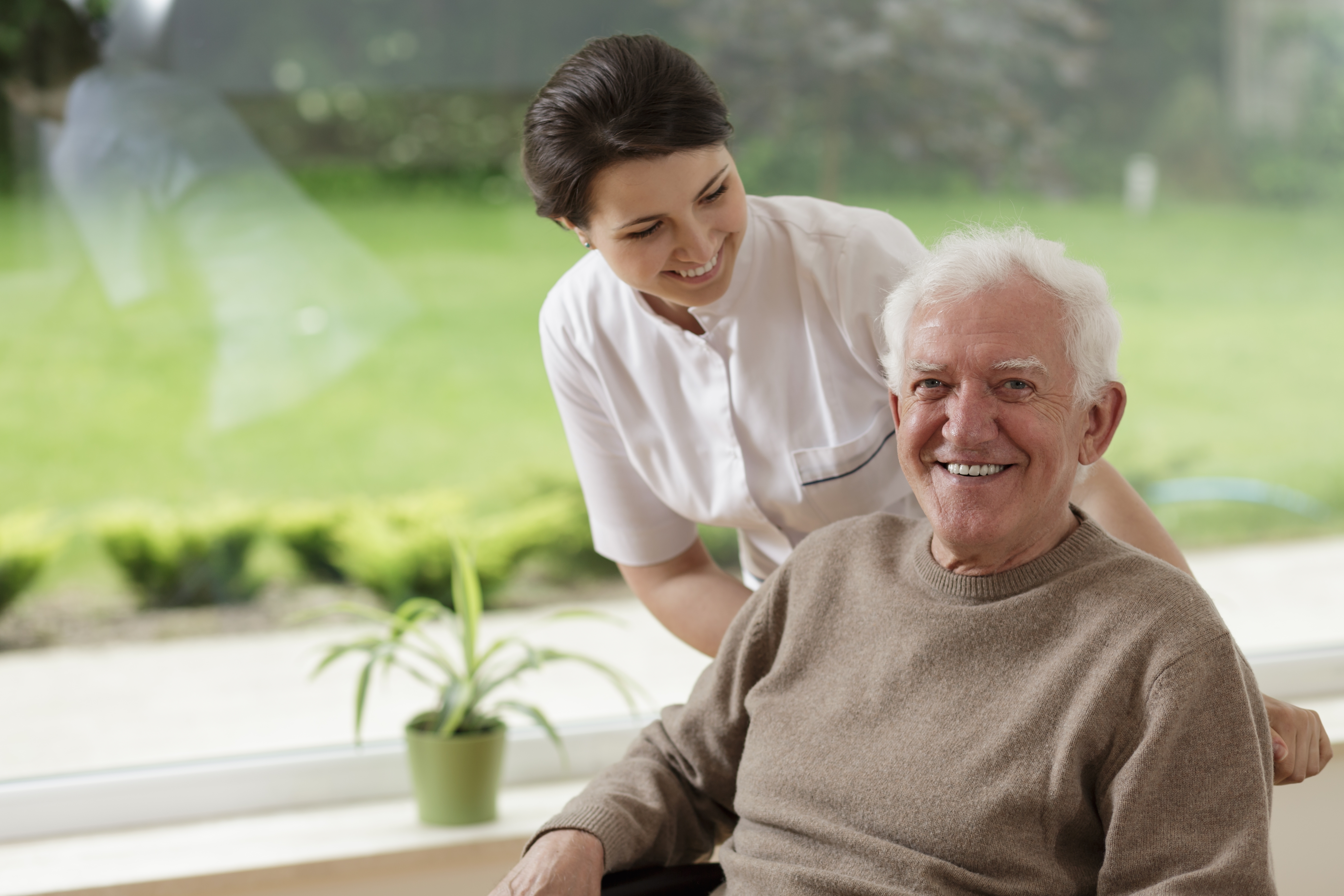 Elderly male with female carer by window
