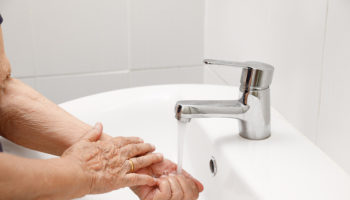 Elderly woman washes hand in bathroom