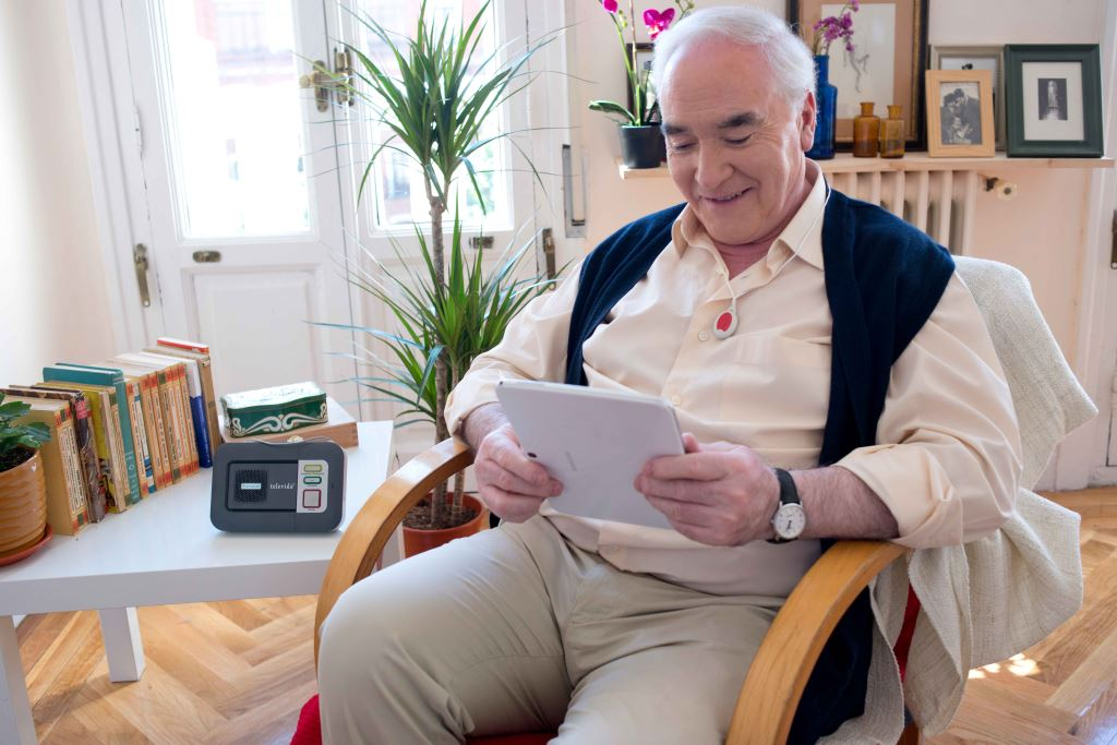 Man-reading-tablet-with-myAmie-and-Lifeline-Vi