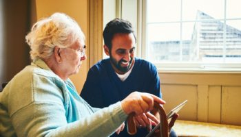 Male nurse showing a digital tablet to an elderly woman