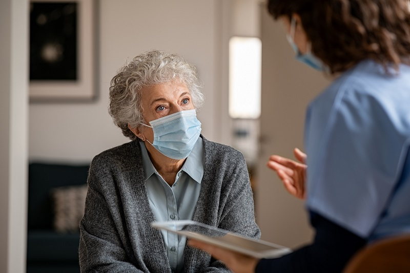 Senior,Woman,Wearing,Safety,Protective,Mask,At,Home,And,Talking